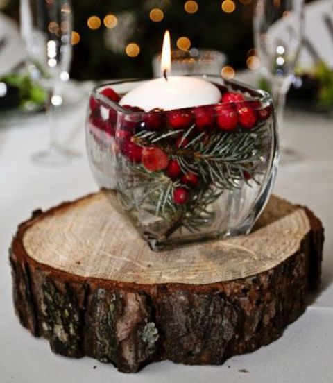 a wooden slice with a glass jar and evergreens, berries and a floating candle