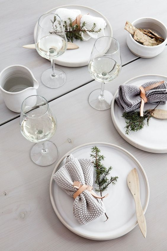 modern Scandinavian-inspired tablescape with evergreens, crochet napkins and a whitewashed table