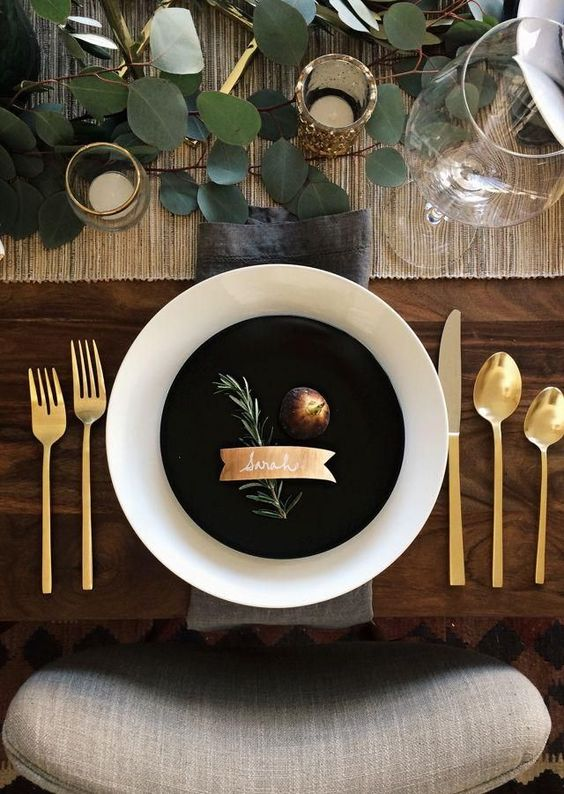 a black plate makes a statement on a table with fresh leaves and gold tableware, rustic touches are cozy
