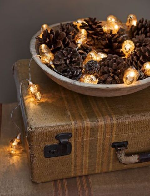 a bowl with pinecones and vintage lights