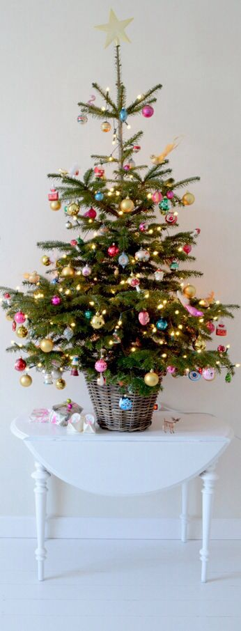a small traditional Christmas tree decorated with colorful ornaments