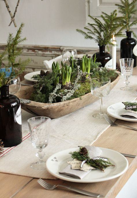 a wooden bowl with moss and bulbs is a perfect centerpiece for a rustic table setting