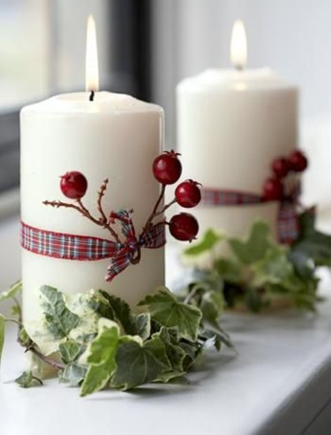 candles wrapped with berries, ribbon and leaves