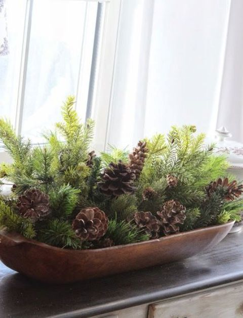 a dough bowl with evergreens and pinecones for a rustic look