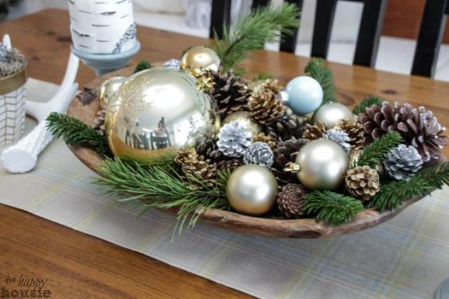 a wooden bowl with pinecones, ornaments and greenery