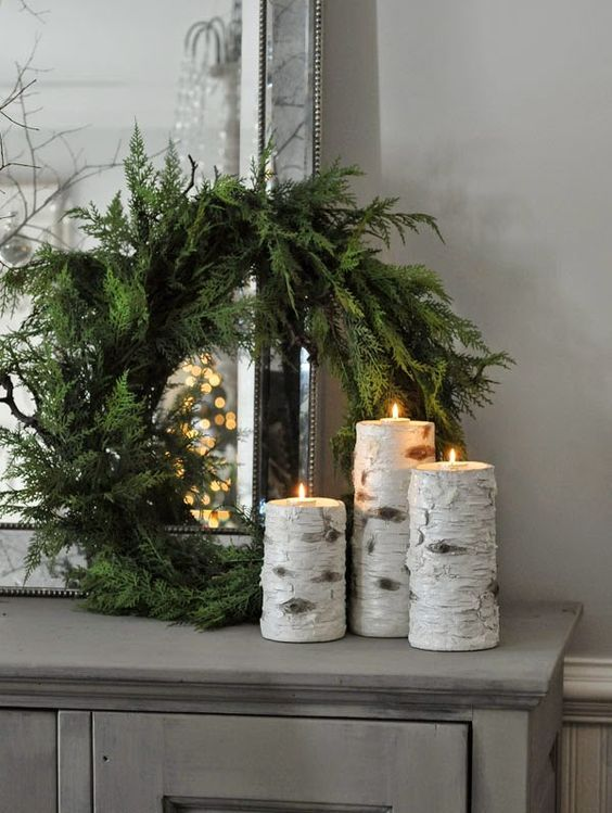 candles wrapped with birch bark and a simpel evergreen wreath