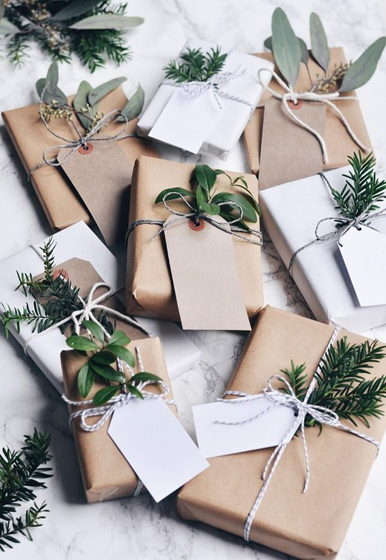 kraft paper with green branches and leaves, twine and gift tags