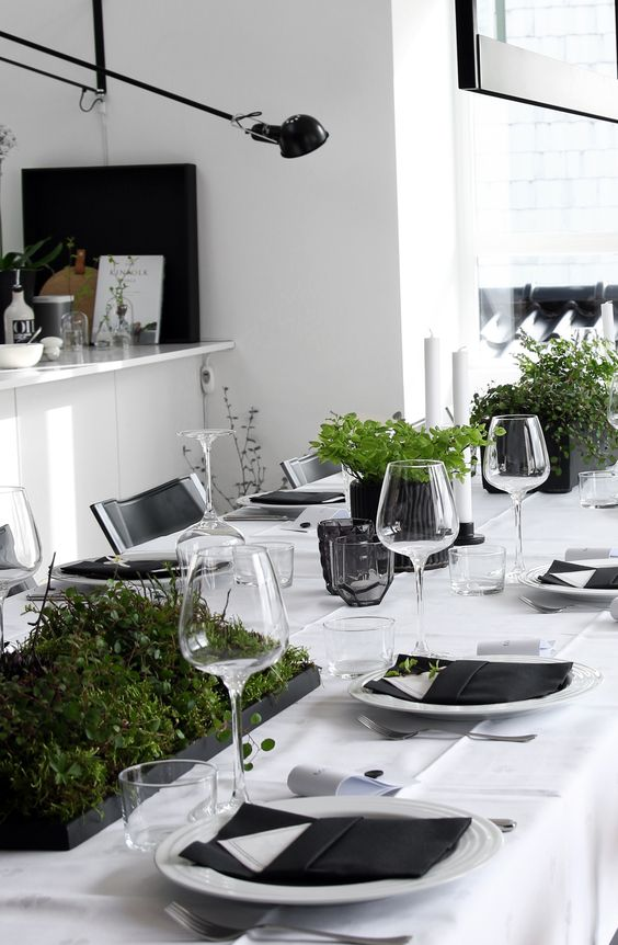 minimalist black and white Christmas tablescape with potted greenery and black napkins