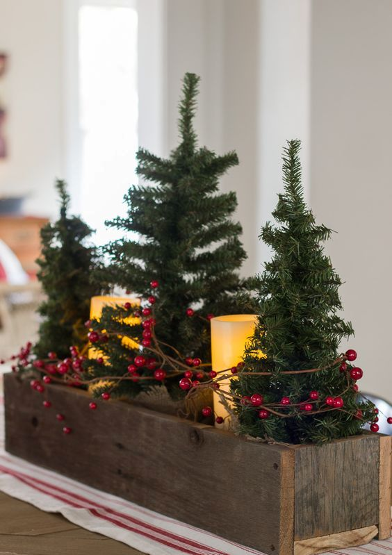 small faux Christmas trees and pillar battery candles wrapped with red grapevine berries in a rustic wooden box