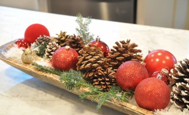 a dough bowl with red ornaments, pinecones and evergrene sprigs