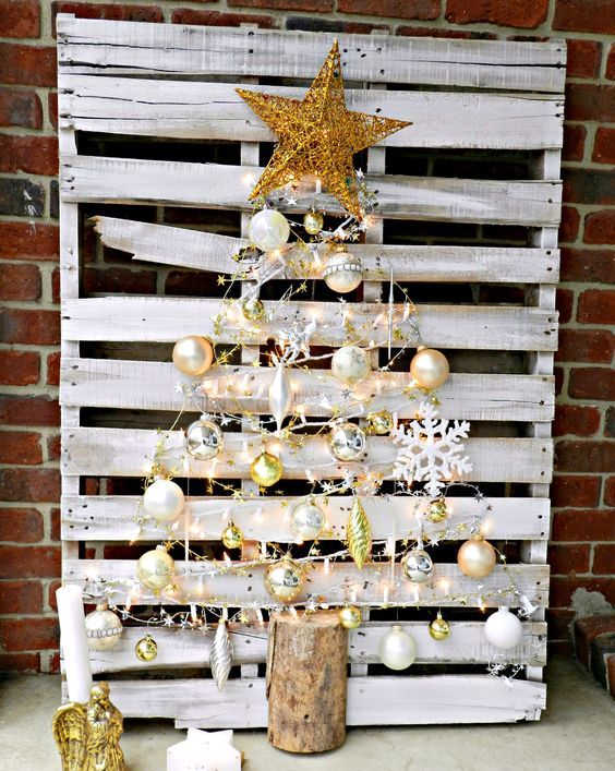 a whitewashed pallet with metallic ornaments that form a tree