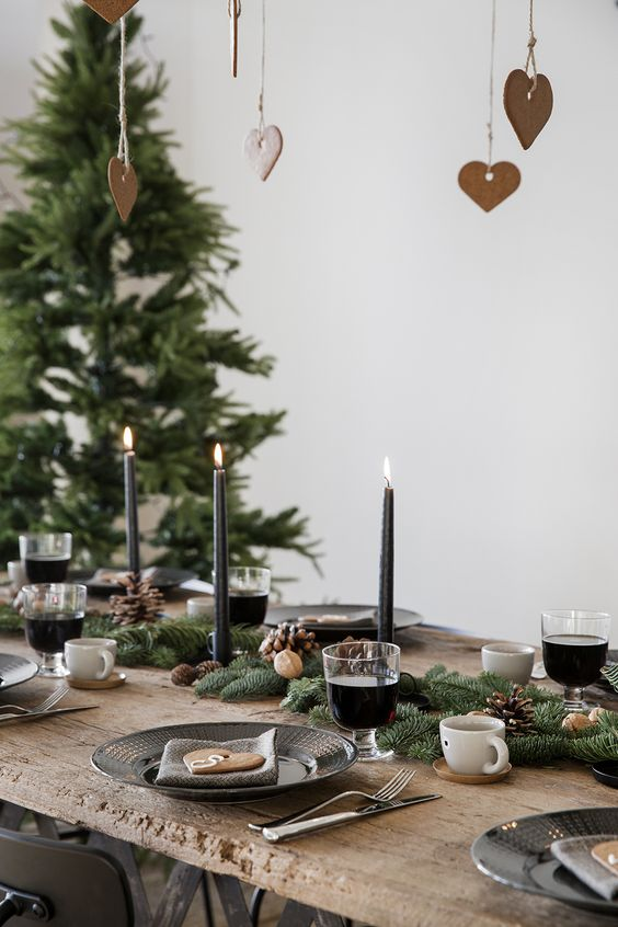 evergreen table runner with nuts, black candles and pinecones