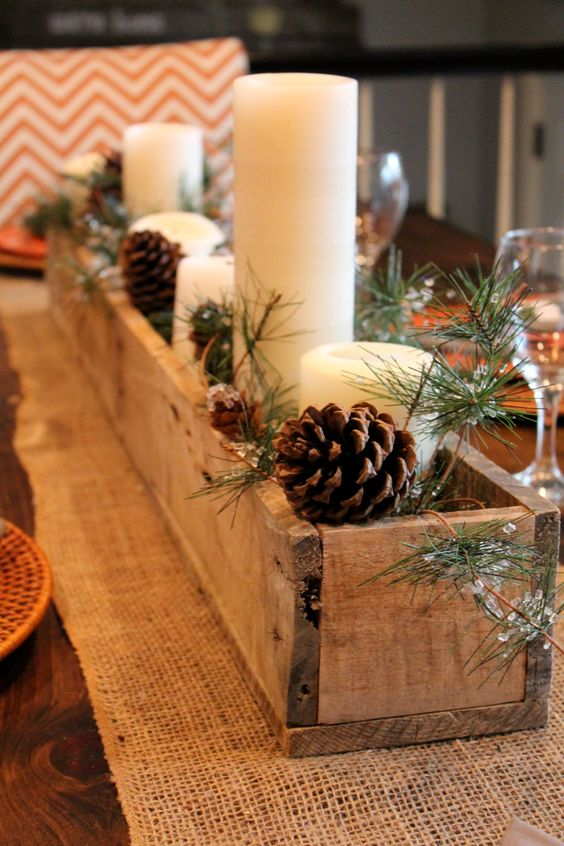 wooden planter with pillar candles, evergreens and pinecones