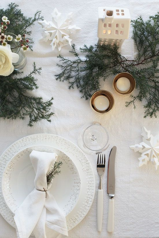 beautiful white table wwith evergreens, paper snowflakes and candles
