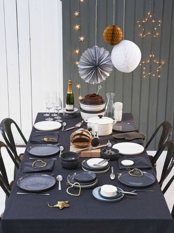 a black tablecloth, gold ornaments and grey plates