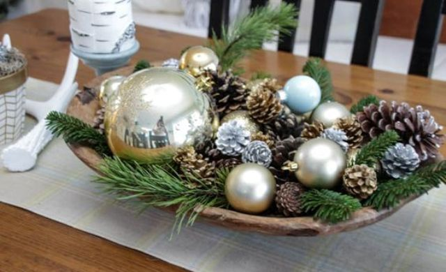 a dough bowl with ornaments, pinecones, evergreens