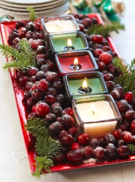 a tray with cranberries and candles as a Christmas centerpiece