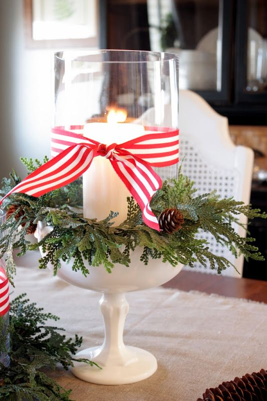 a candle jar wrapped with faux greenery, pinecones and striped ribbon