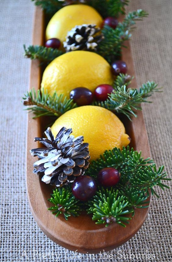 a long wooden tray with evergreens, lemons, cranberries and pinecones
