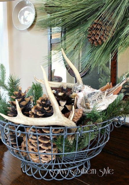 a wire bowl with antlers, pinecones and evergreens