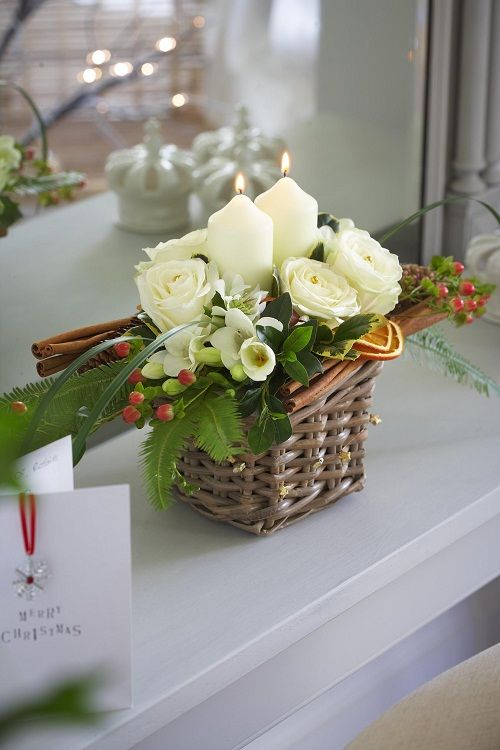 an ivory and green arrangement with citrus in a small basket is perfect for rustic Christmas table setting