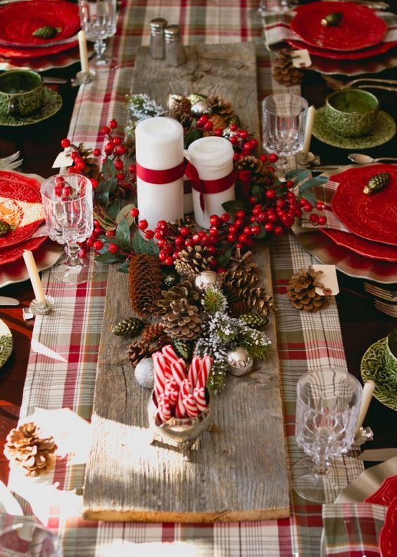 candles with ribbons and pinecones on a wooden board as a centerpiece