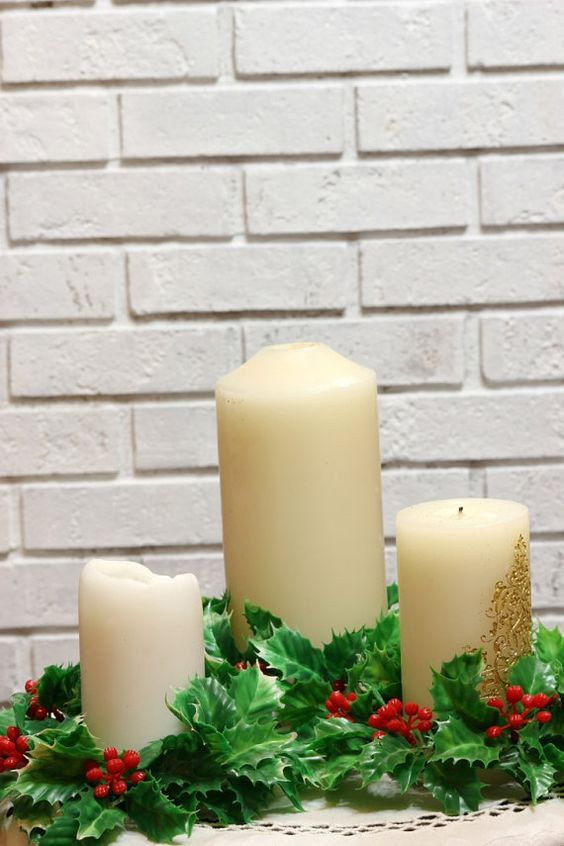cover the candles with holly leaves and berries