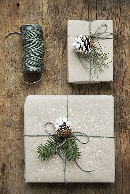 kraft paper, green yarn, evergreen twigs and snowy pinecones