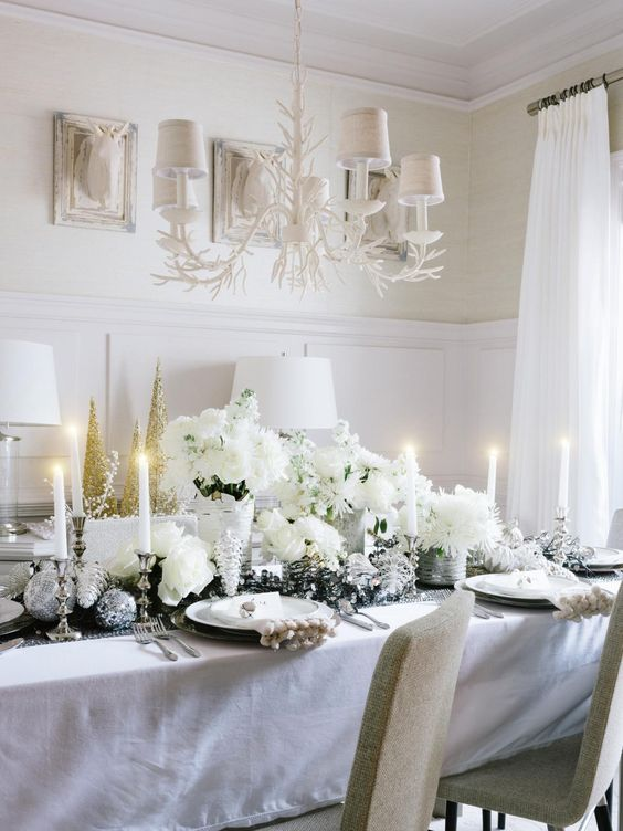 lush white tablescape with silver decorations and lots of florals