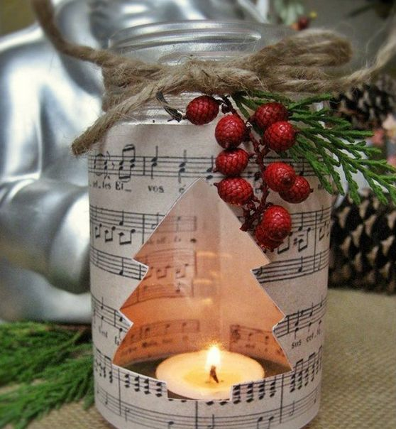 a candle lantern with music paper, faux berries and evegreens