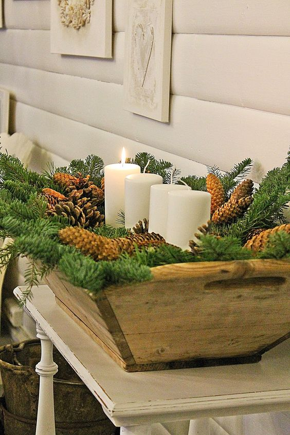 a large wooden bowl filled with pinecones, evergreens and pillar candles