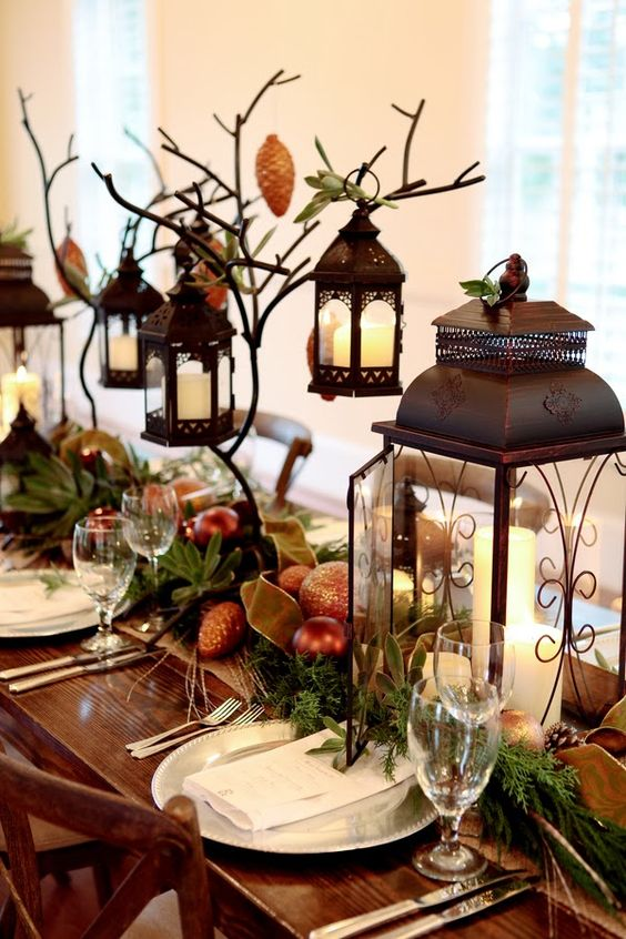 lush table runner with evergreens, ornaments, candle lanterns and pinecones