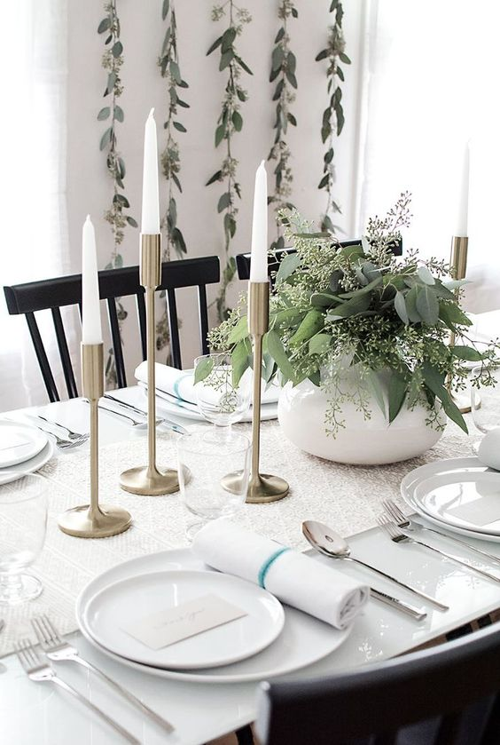modern rustic white table with brass candle holders and eucalyptus branches in pots