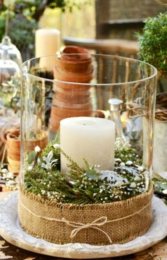 a large glass lantern with evergreens and a candle, wrapped with burlap