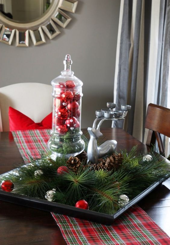 a tray with evergreens, small ornaments, pinecones and a deer