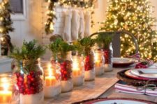 11 faux snow and cranberries and evergreens in jars as a table runner