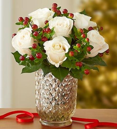 winter white roses are paired with festive red hypericum berries and put in a mercury glass