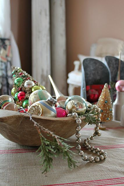 a dough bowl with vintage ornaments and beads