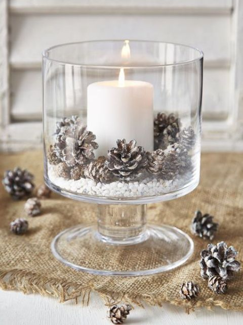 a large glass with snowy pinecones and a candle