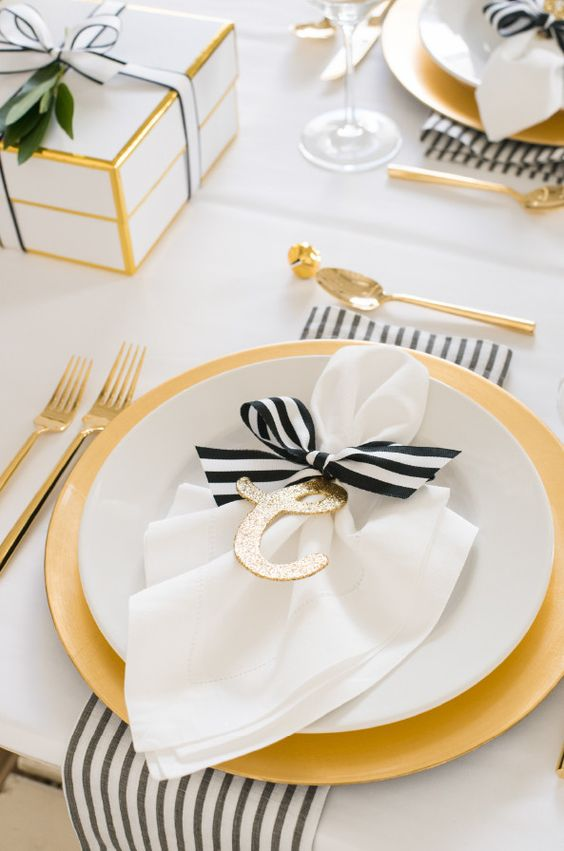 black and white table setting is spruced up with gold and glitter touches