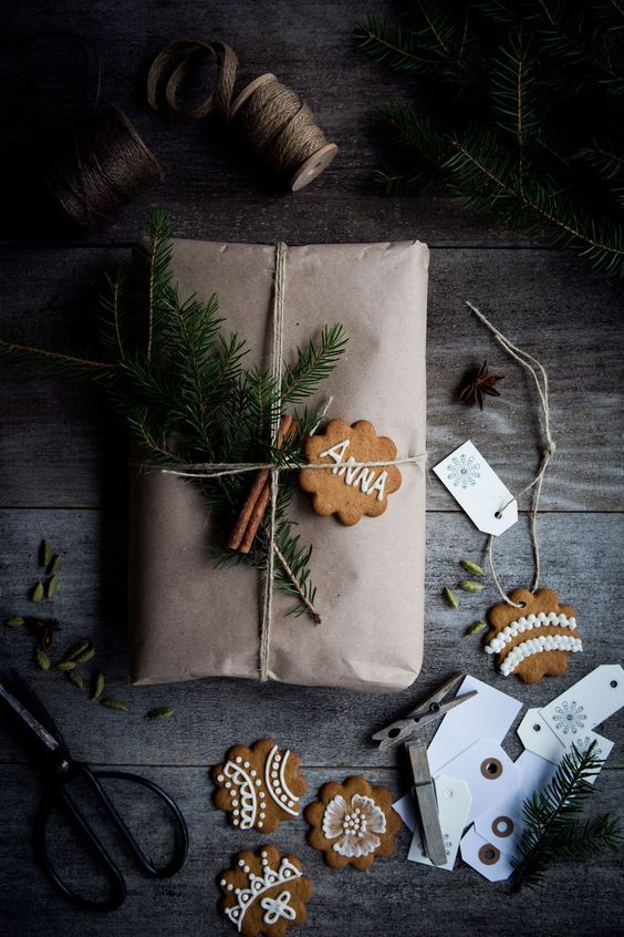 kraft paper, evergreens, cinnamon sticks and a cookie as a gift tag
