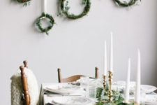 12 white tablescape is spruced up with an evergreen table runner and gold candle holders