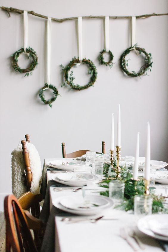 white tablescape is spruced up with an evergreen table runner and gold candle holders