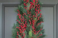 13 a small evergreen tree with holly berries and a bow instead of a usual wreath