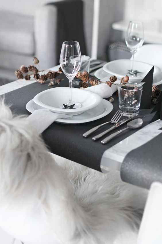 black and white table with black placemats and pinecones