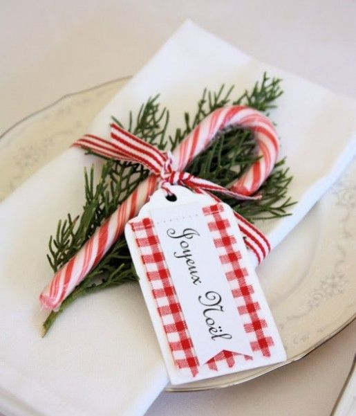 striped ribbon, rosemary and a candy cane for decorating a napkin