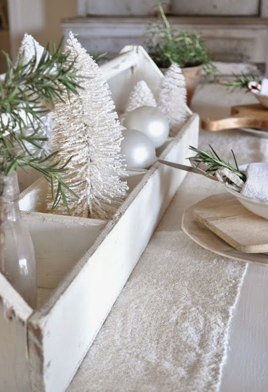 white rustic tablescape with a bleached toolbox with small trees and a white fabric table runner