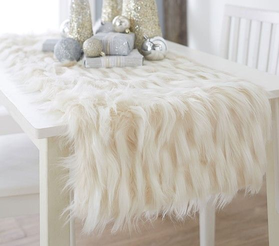 a fur table runner with silver and gold Christmas decorations