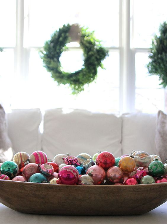 a primitive dough bowl filled with colorful vintage ornaments