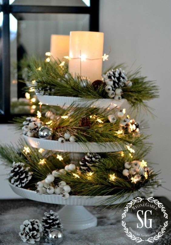 tiered tray with star lights, evergreens, pinecones and candles